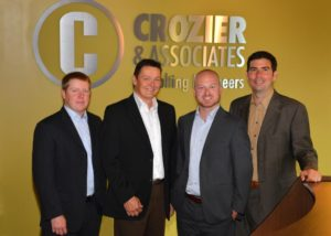 Chris Crozier (second from left) welcomes staff members Jon Proctor (on left), Chris Boyce and Alex Fleming to the firm's Associate Group.