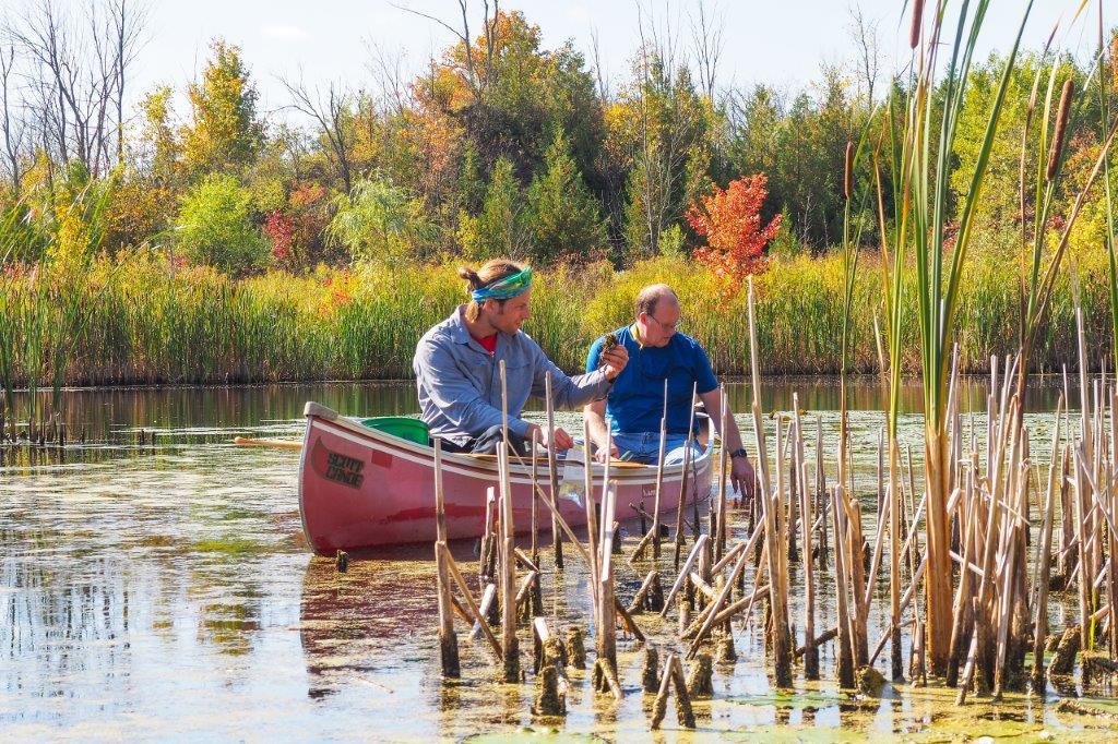 Men in canoe retrieving water for testing
